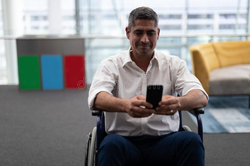 Caucasian disabled businessman using mobile phone while sitting on wheelchair in office stock images