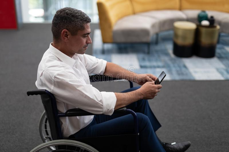 Caucasian disabled businessman using mobile phone while sitting on wheelchair in office stock image