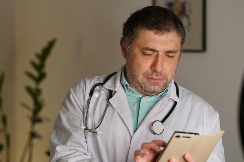 Portrait of a doctor texting on his mobile phone royalty free stock image