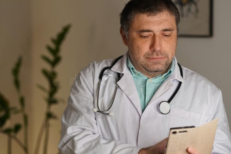 Portrait of a doctor texting on his mobile phone royalty free stock photography