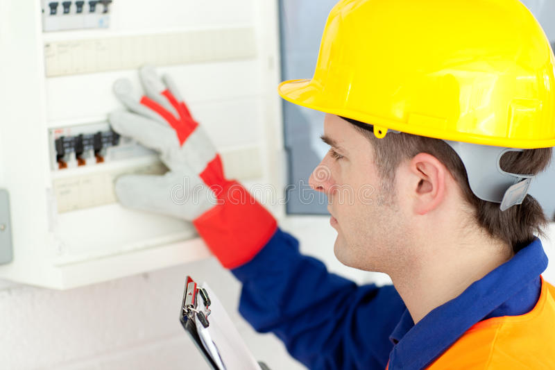 Caucasian electrician repairing a power plan stock photo