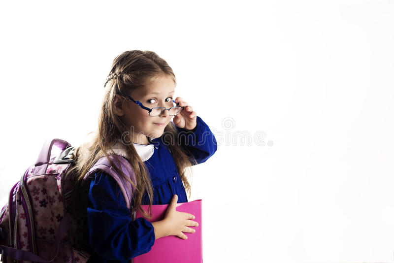 Caucasian elementary age schoolgirl with glasses posing in unifo. Rm and backpack on white background. School and education concept stock photography