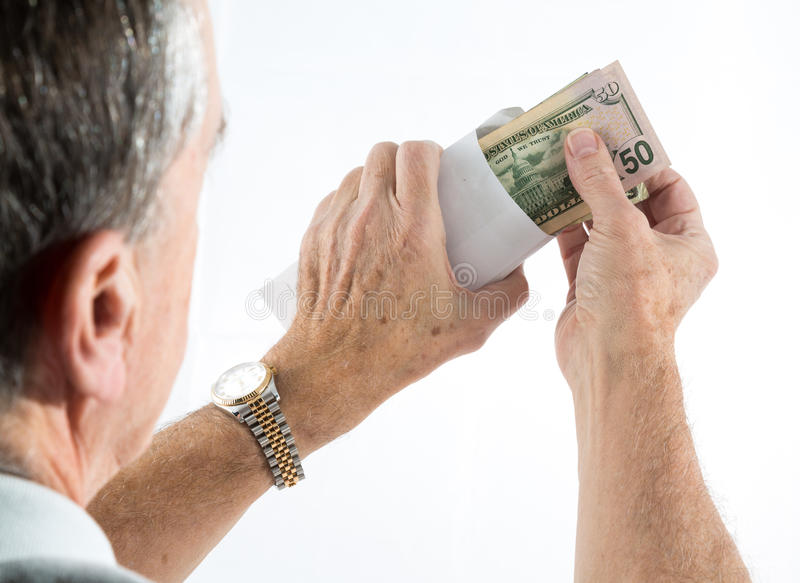 Caucasian ethnicity hands putting fifty dollar bills in envelope. Stack of fifty and twenty US dollar bills being put in envelope by senior caucasian hands with stock image