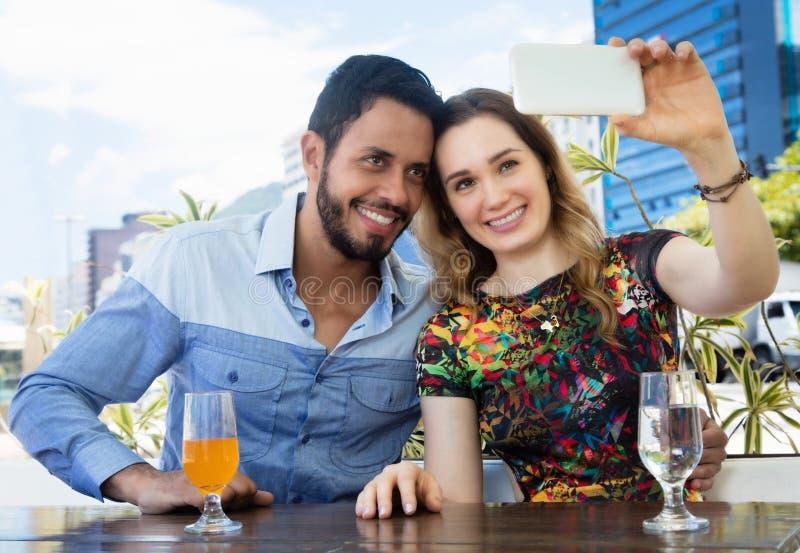 Caucasian förälskelsepar i semestern som tar selfie med telefonen som är utomhus- i sommaren arkivbilder