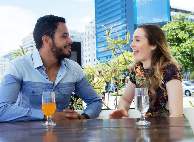 Caucasian förälskelsepar som talar i en restaurang som är utomhus- i sommaren royaltyfri foto