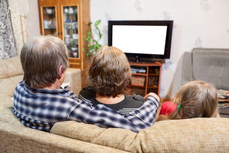 Caucasian fader-, moder- och dottersammanträde på soffan och hållande ögonen på tv, isolerade den vita skärmen royaltyfria bilder