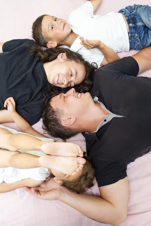 Caucasian familj av fyra som har gyckel, medan ligga på Sofa Indoors fotografering för bildbyråer