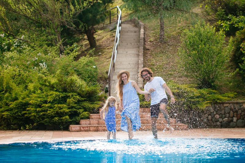 Family having fun their pool. family splashing water with legs or hands in swimming pool stock image