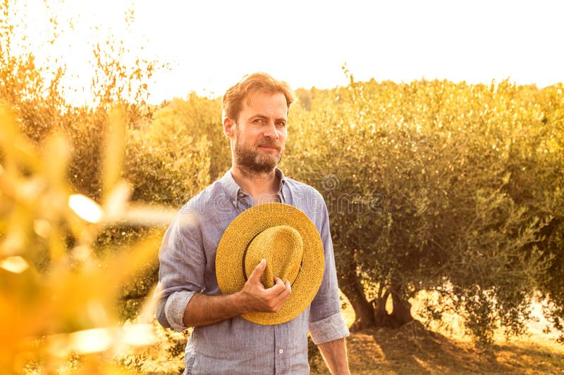 Farmer standing in front of a olive grove - agriculture. Caucasian farmer or gardener with a straw hat standing proud in front of an olive grove. Agriculture or stock images