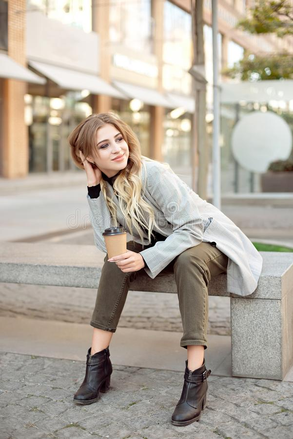 Caucasian fashion woman with cup of coffee sitting near storefront shop windows on the street outdoors. Have a rest during coffee break stock photos