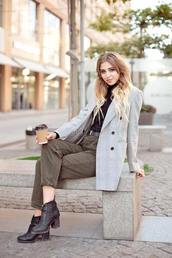 Caucasian fashion woman with cup of coffee sitting near storefront shop windows on the street outdoors. Have a rest during coffee break royalty free stock photos