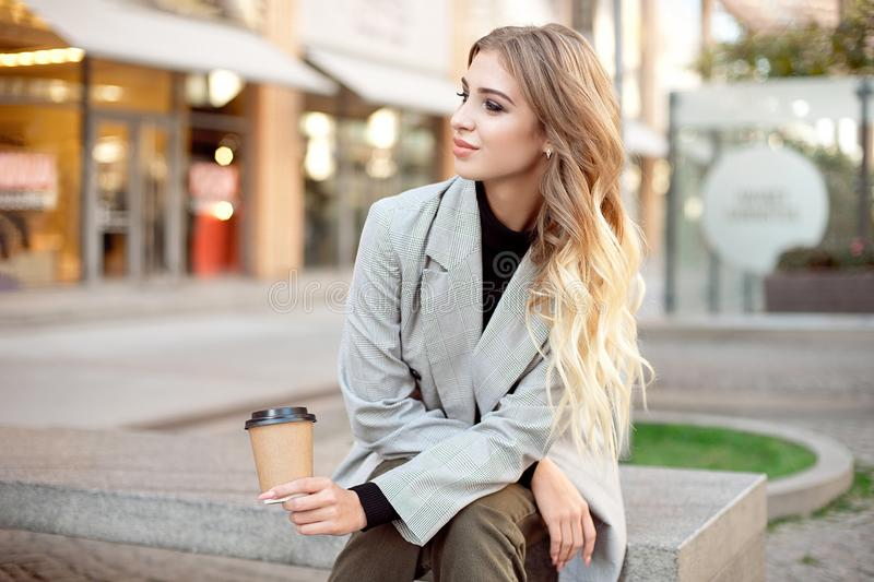 Caucasian fashion woman with cup of coffee sitting near storefront shop windows on the street outdoors. Have a rest during coffee break stock images