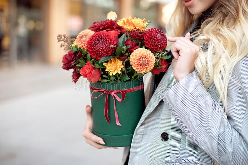 Caucasian fashion woman standing on the street near storefront shop windows holding flower-box with happy smile.  royalty free stock photos