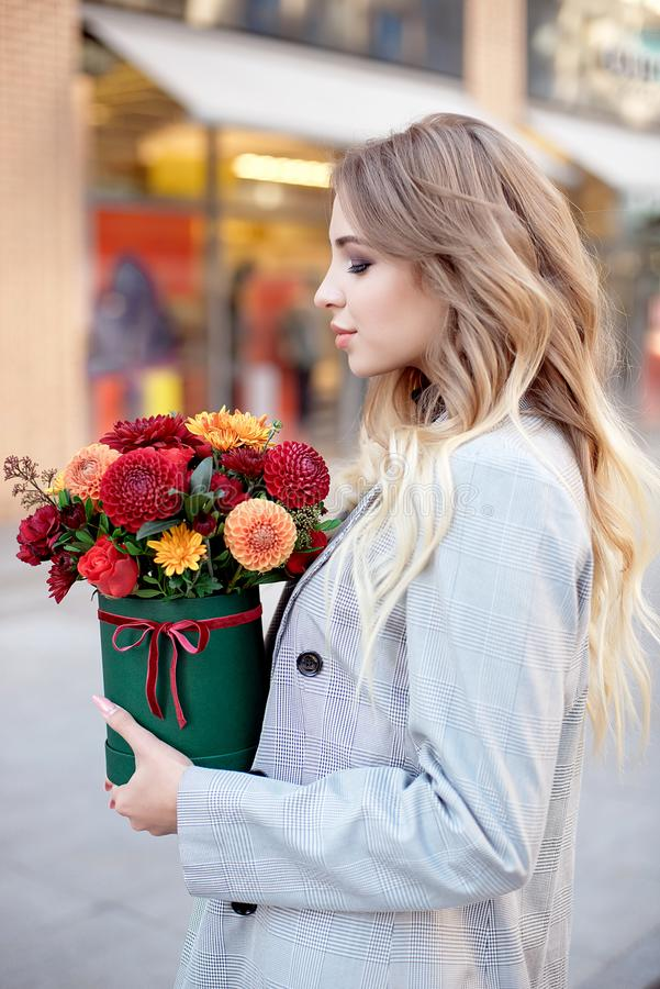 Caucasian fashion woman standing on the street near storefront shop windows holding flower-box with happy smile.  royalty free stock images