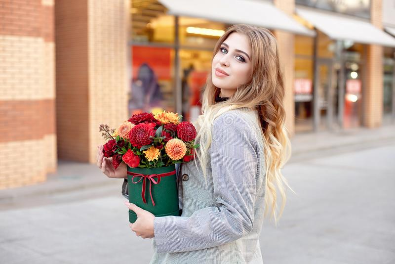 Caucasian fashion woman standing on the street near storefront shop windows holding flower-box with happy smile.  royalty free stock image