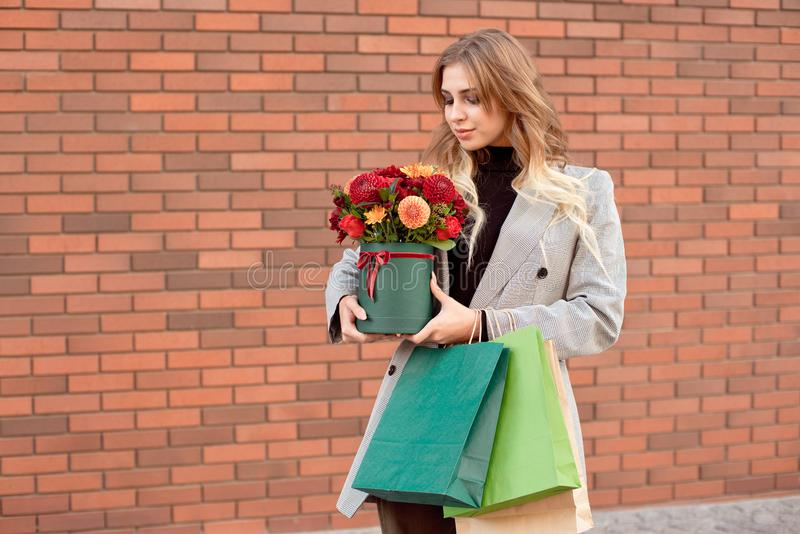 Caucasian fashion woman standing on the street near storefront shop windows holding flower-box with happy smile.  stock image