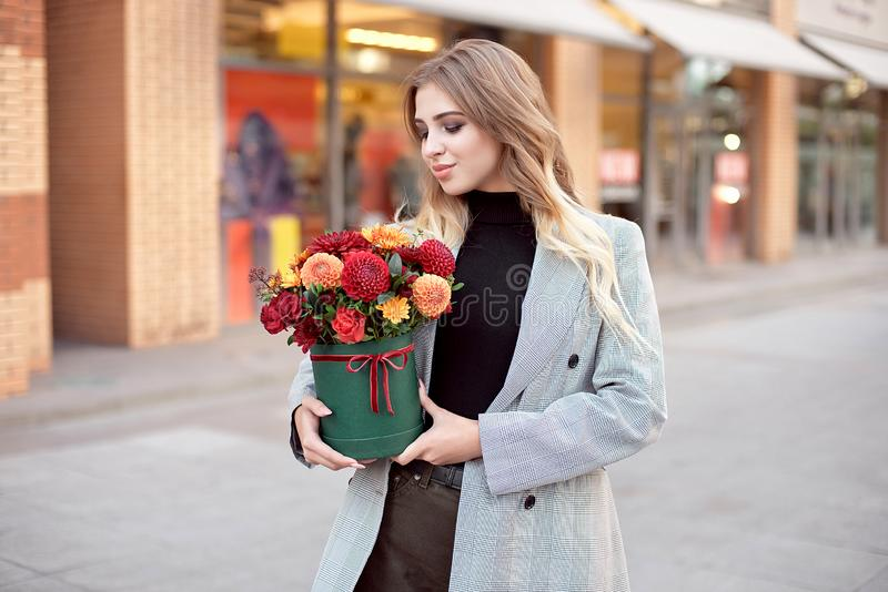 Caucasian fashion woman standing on the street near storefront shop windows holding flower-box with happy smile.  royalty free stock photography