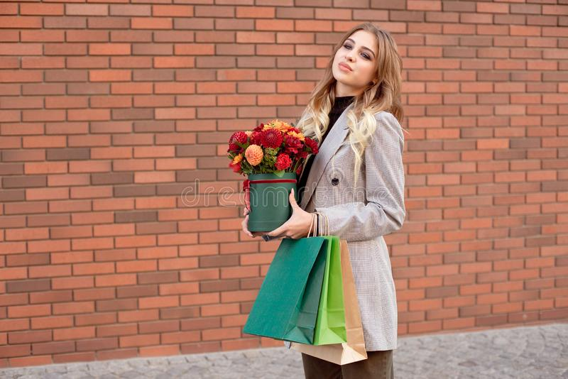 Caucasian fashion woman standing on the street near storefront shop windows holding flower-box with happy smile.  royalty free stock photo
