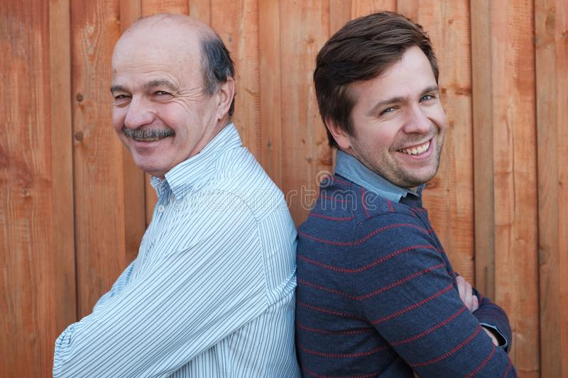 Caucasian father and adult son smiling and looking at camera royalty free stock image