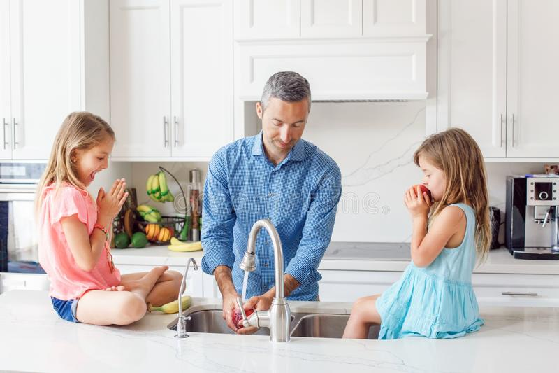 Caucasian father dad gives children daughters fresh fruits to eat royalty free stock photos