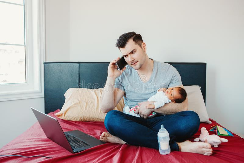 Caucasian father dad with newborn mixed race Asian Chinese baby working from home stock images