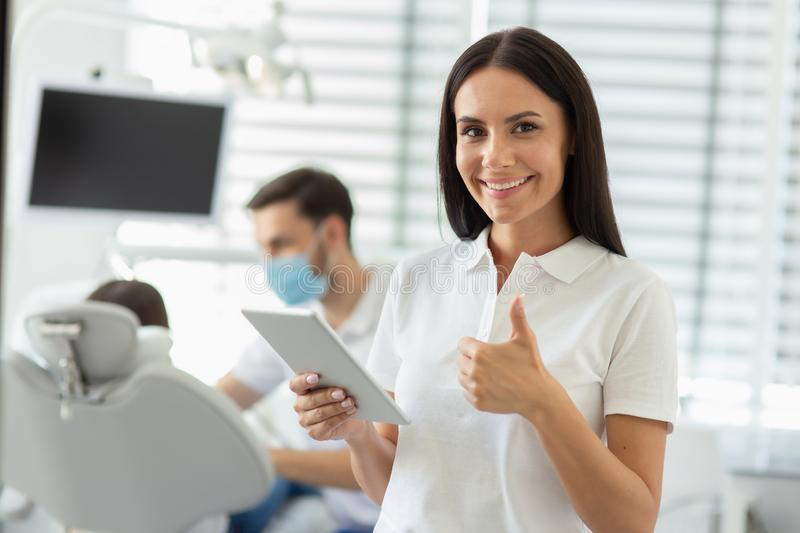 Caucasian female doctor showing thumb up, holding digital tablet and smiling at the camera with colleague working with client on stock photography