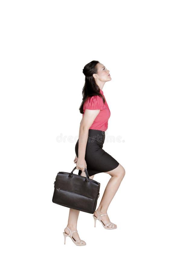 Caucasian female entrepreneur step upward on studio. Caucasian female entrepreneur carrying a briefcase while posing to step upward, isolated on white background stock image