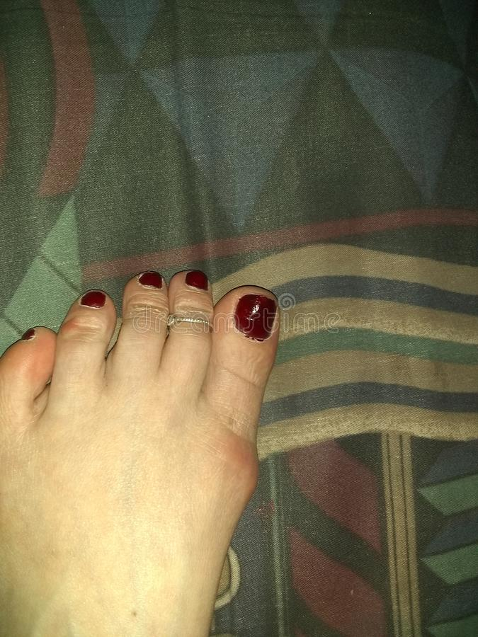 Caucasian female foot with maroon red nail polish and Sterling silver toe ring, geometric shapes in the background. Caucasian female foot with maroon red nail stock images