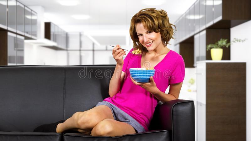 Woman Eating Breakfast on a Couch stock photography