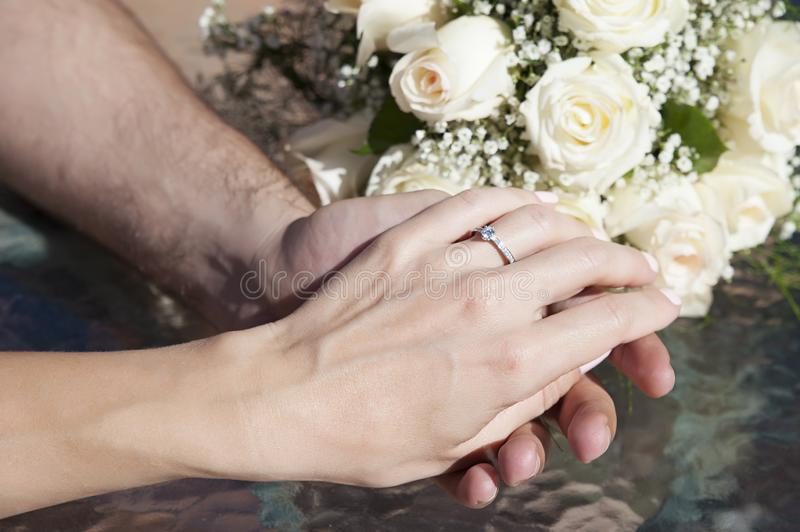 Caucasian female and male, delicately holding hands, with visible engagement ring on the woman`s finger stock photo