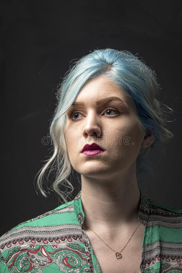 Caucasian female model, Age 22, Blue dyed hair, Red lips, green and red shirt. Isolated on black background. Upper torso. Belly ex stock image