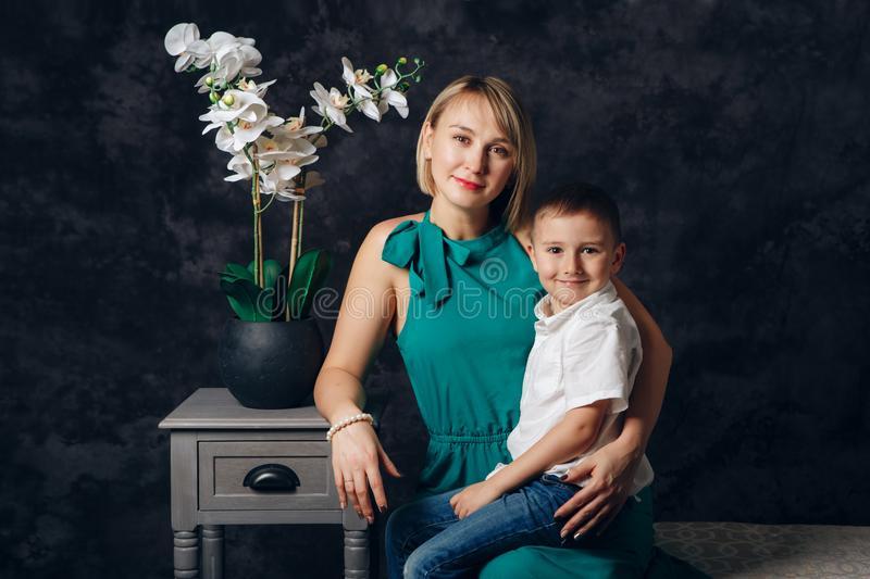 Caucasian female parent and son prescholler boy sitting together on couch indoors. Happy mother day holiday royalty free stock photo