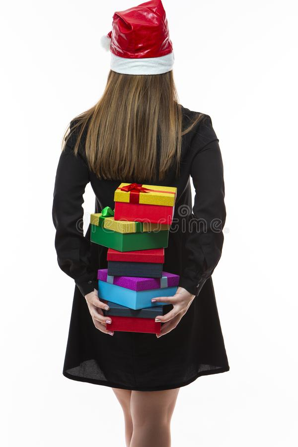 Caucasian Female In Santa Hat Holding Heap of Colorful Giftboxes with Ribbons Behind Her Back. Isolated Over White stock photos