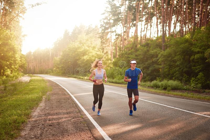 Caucasian female sports woman and fit man in full body length running pine forest road. healthy lifestyle concept stock photo