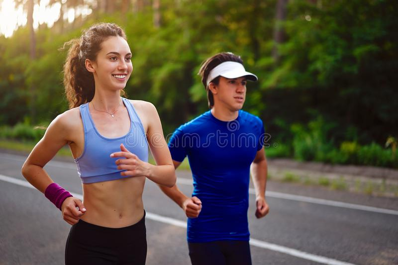 Caucasian female sports woman and fit man in full body length running pine forest road. healthy lifestyle concept royalty free stock image