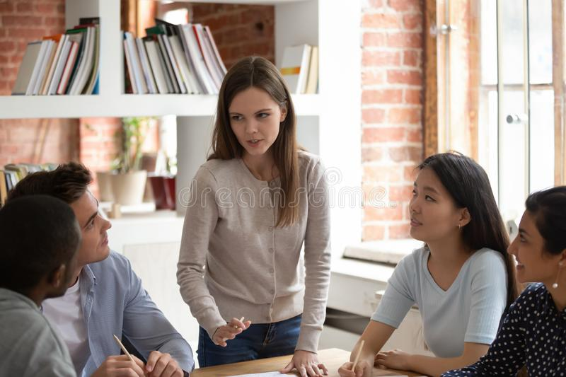 Caucasian female team leader speak at meeting with groupmates royalty free stock photography