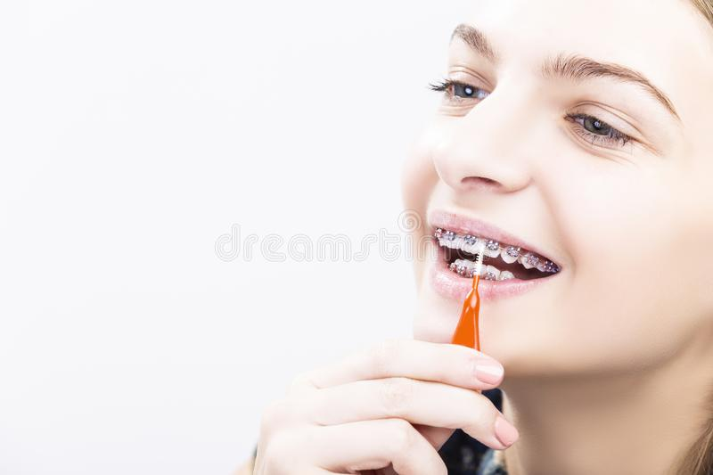 Caucasian Female Teenage Girl With Brackets. Dental Health Ideas and Concepts.Smiling Caucasian Female Teenager With Teeth Braces. Cleaning Brackets Using stock photos
