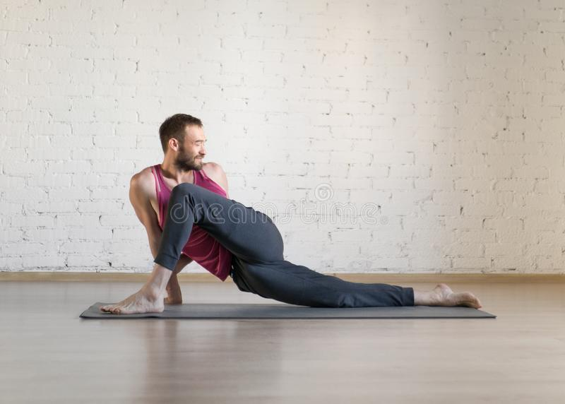 Caucasian fit man doing warm-up stretching on grey mat in fitness studio, twisted pose, selective focus. Pilates, yoga, male health, workout, exercise therapy stock photo