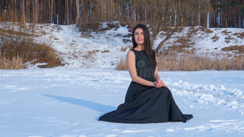 Caucasian flicka för ung brunett som ler i en svart klänning på snön arkivbilder