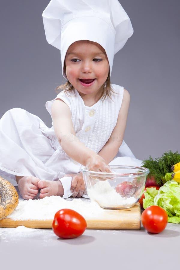 Caucasian flicka i kocken Uniform Preparing Courses med mjöl och grönsaker i studio arkivfoto
