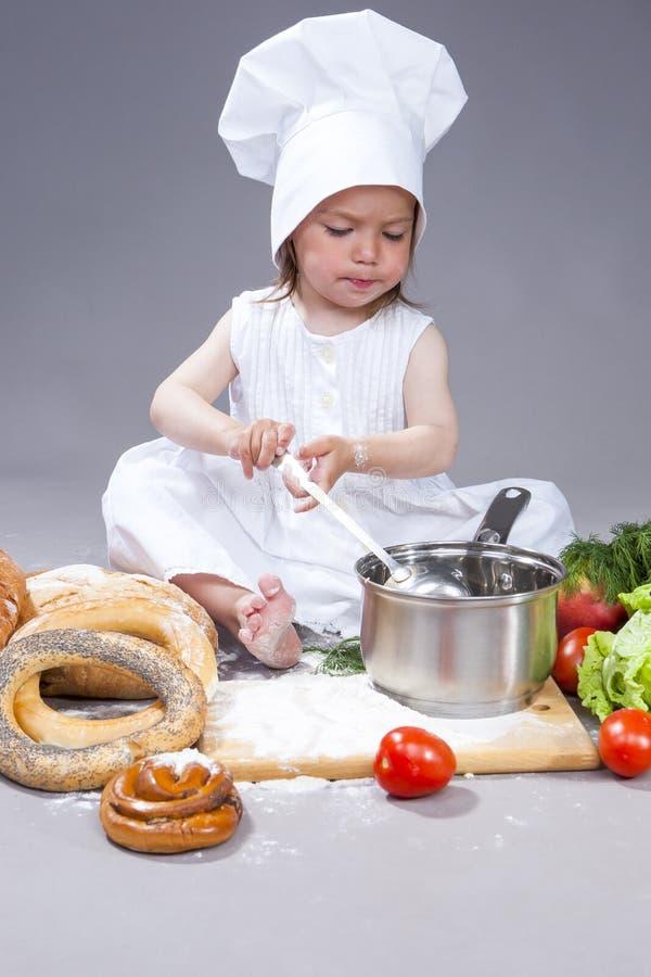 Caucasian flicka i kocken Uniform Preparing en soppa och framställning av en blandning med skopan arkivbilder