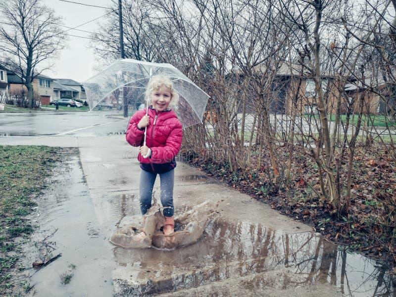 Caucasian flicka som hoppar i p?lar som utanf?r g?r f?rgst?nk under regn p? v?rh?stdag arkivfoton