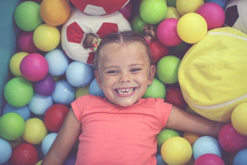 Caucasian flicka som ligger på kulör boll Liten flicka som spelar i plommoner royaltyfri bild
