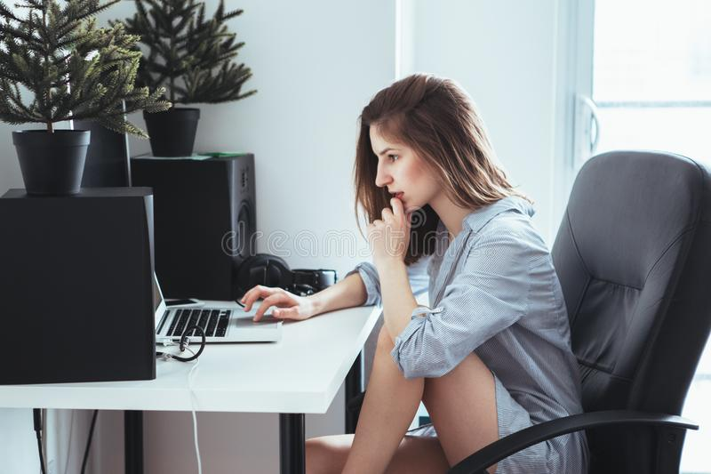 Caucasian flickakvinnastudent i pyjamasskjortan som arbetar på bärbar datordatoren arkivbild