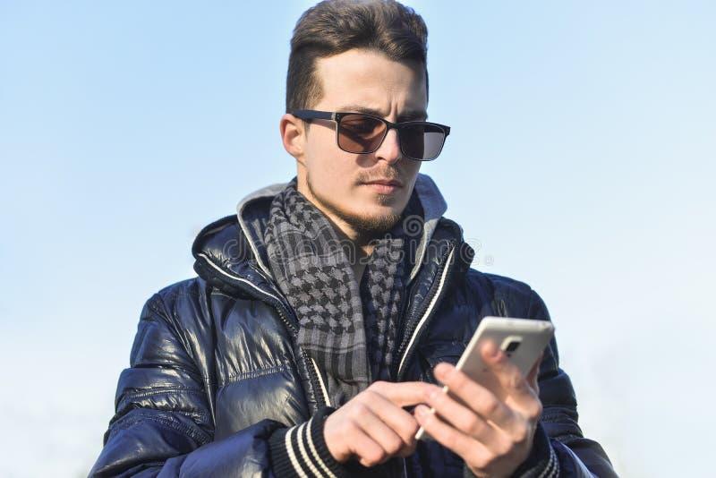 Caucasian gemene man som pratar på telefonen med ett leende på gatan royaltyfri fotografi