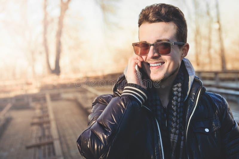 Caucasian gemene man som talar på telefonen med ett leende på gatan royaltyfria foton