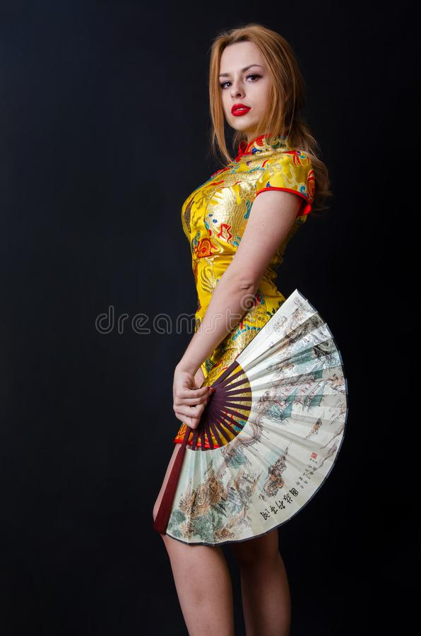 Caucasian girl with Chinese dress and fan royalty free stock photo