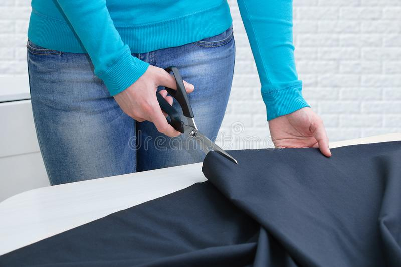 Caucasian girl cuts black cloth on the table. In room. Close-up royalty free stock photo