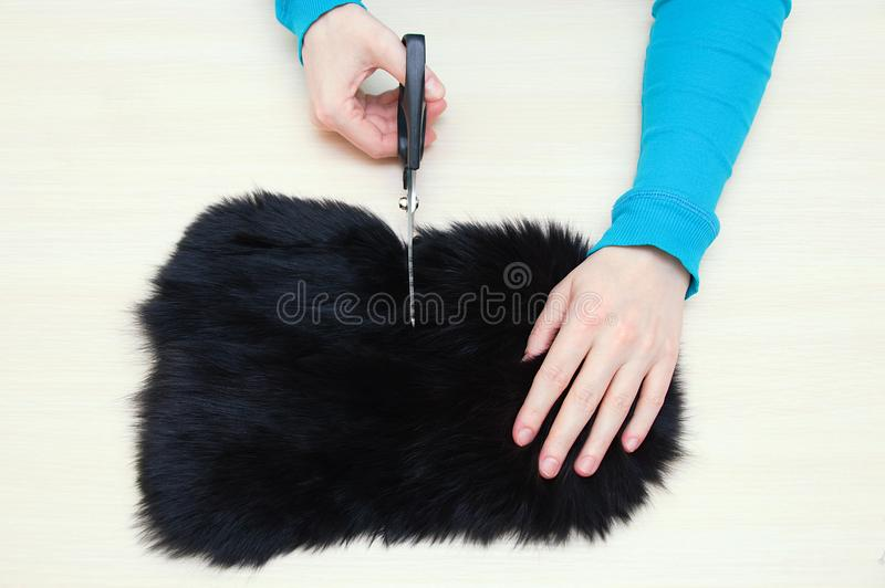 Caucasian girl cuts fur skin with black scissors on the table. stock photos