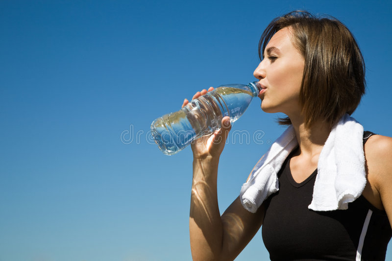 Caucasian girl drinking water after exercise royalty free stock image